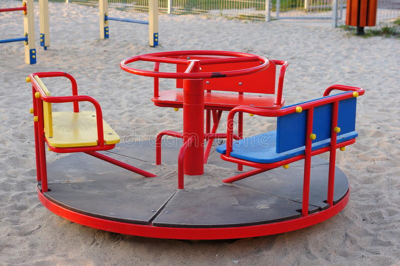 Play ground roundabout. Red roundabout on sand at a play ground stock photography