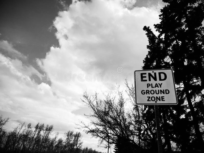 Play ground sign outside. Black and white photo of a sign, end play ground zone, trees and clouds, spring time, trees starting to bloom, local, outside royalty free stock images