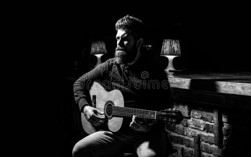 Play the guitar. Beard hipster man sitting in a pub. Guitars and strings. Bearded man playing guitar, holding an royalty free stock images