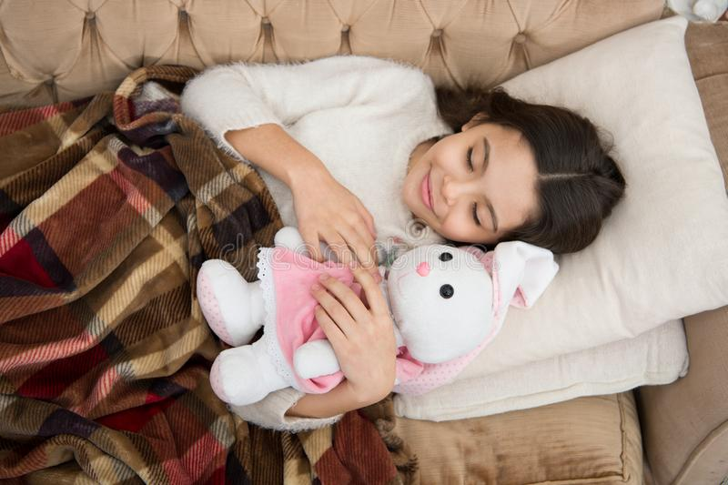 Play soft toy before go sleep. Sleep with toy. Girl enjoy evening time with favorite toy. Kid lay bed and hug bunny toy. Couch pillow blanket background top stock images