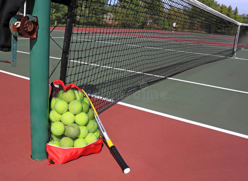 Tennis Courts. A bag of tennis balls and racket on tennis courts tp play tennis royalty free stock image