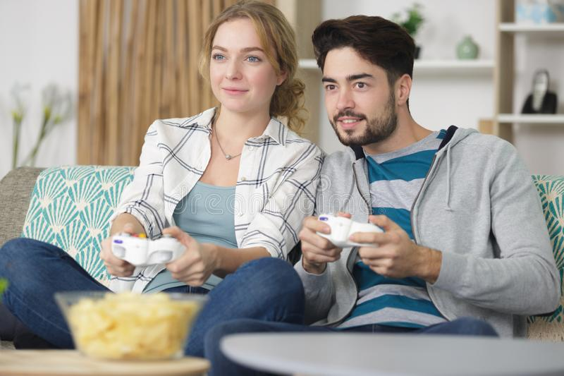 Play video games in their apartment stock photos