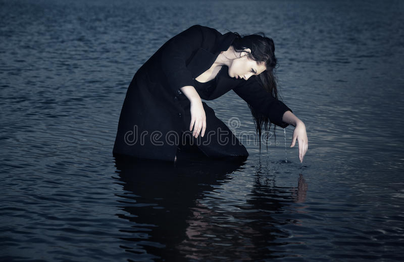 Play with water. Wet lady in the coat playing with water royalty free stock image