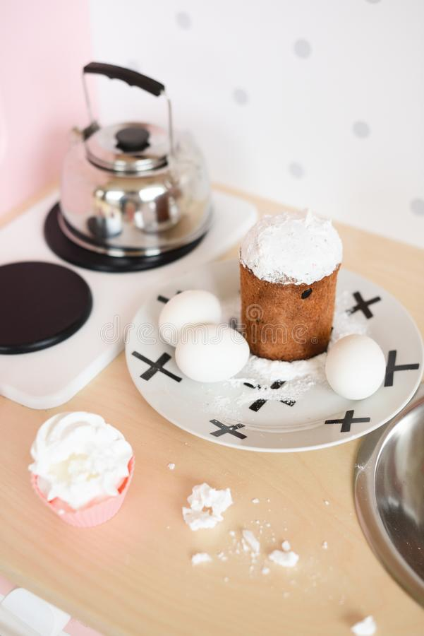 Play wooden furniture for children. Cakes and eggs on table and kettle on kitchen stove stock images