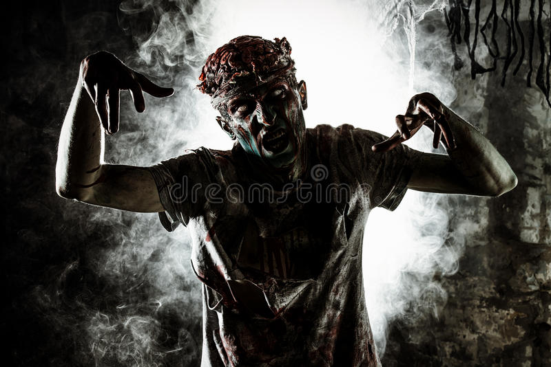 Play in zombie. Terrible bloody zombie man with the brains out in search of his victim. Horror. Halloween concept royalty free stock images