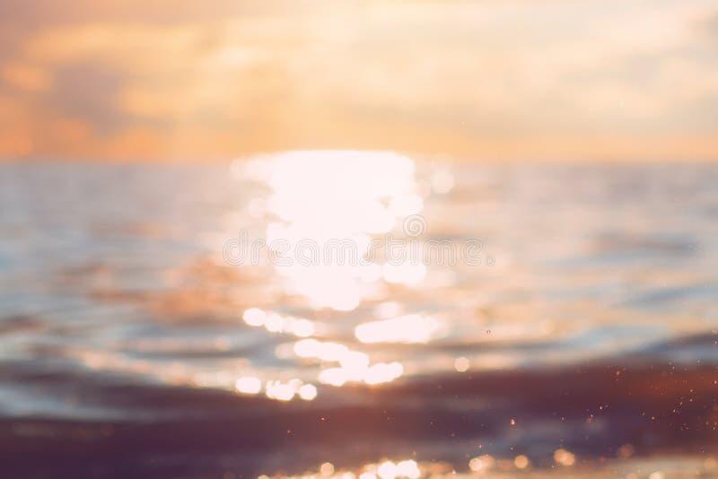 Playa abstracta y onda suave con puesta del sol foto de archivo