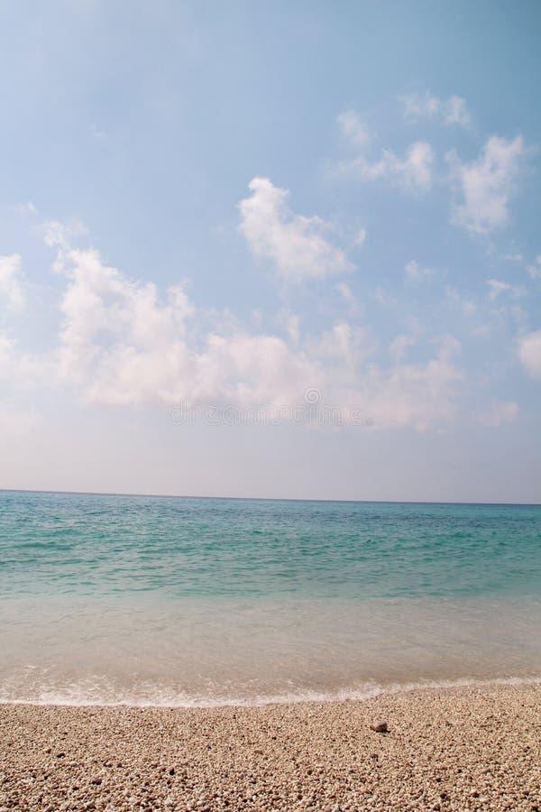 Playa arenosa exótica, mar Mediterráneo tropical con las ondas y la espuma del mar, cielo azul y nubes Ambiente natural, paisaje fotos de archivo