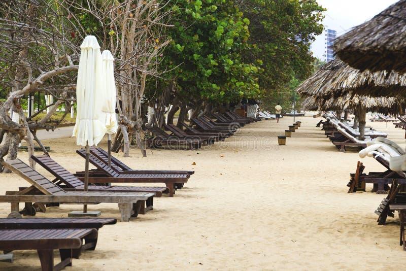 Playa arenosa sola con las sillas y los paraguas de playa cerca del mar foto de archivo libre de regalías