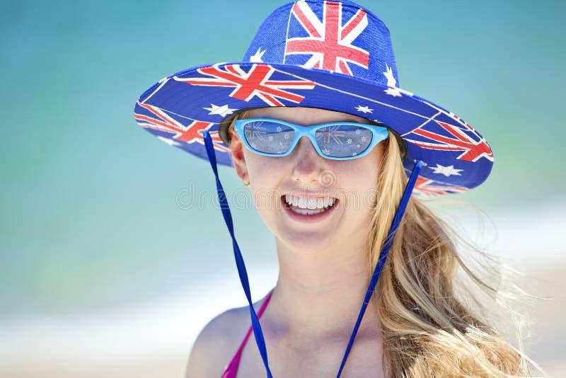 Playa australiana de la muchacha del sombrero de la bandera fotos de archivo libres de regalías