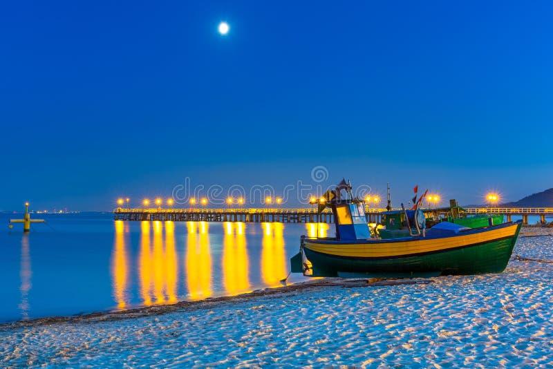 Playa báltica con el barco de pesca en la noche imagen de archivo libre de regalías