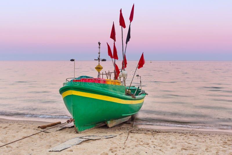 Playa báltica con el barco de pesca en la puesta del sol fotos de archivo libres de regalías