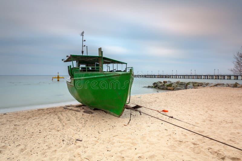 Playa báltica en Gdynia Orlowo con el barco de pesca en el amanecer, Polonia foto de archivo