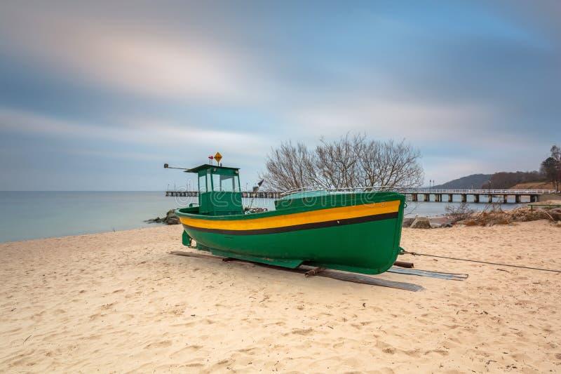 Playa báltica en Gdynia Orlowo con el barco de pesca en el amanecer, Polonia fotografía de archivo