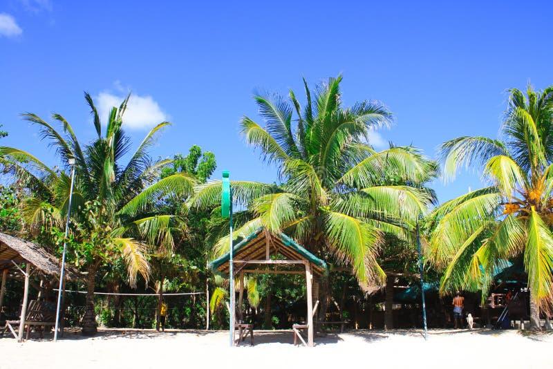 Playa blanca de la arena contra el cielo azul claro con los árboles de coco de la palma y las chozas altos de la playa fotos de archivo