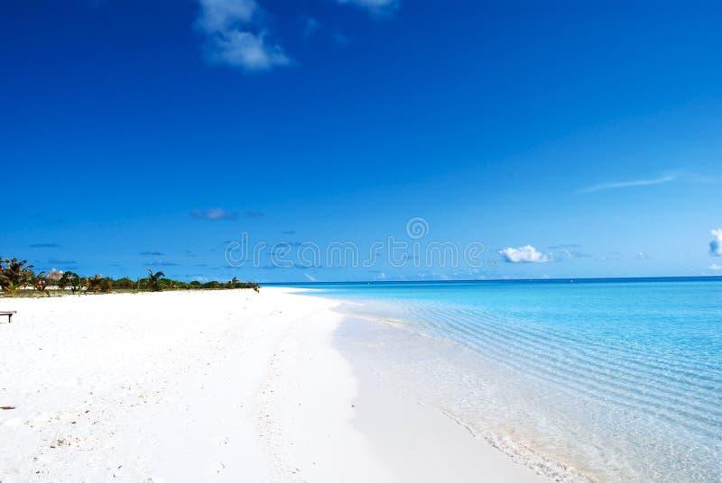 Playa blanca de la arena y cielo azul azul fotos de archivo