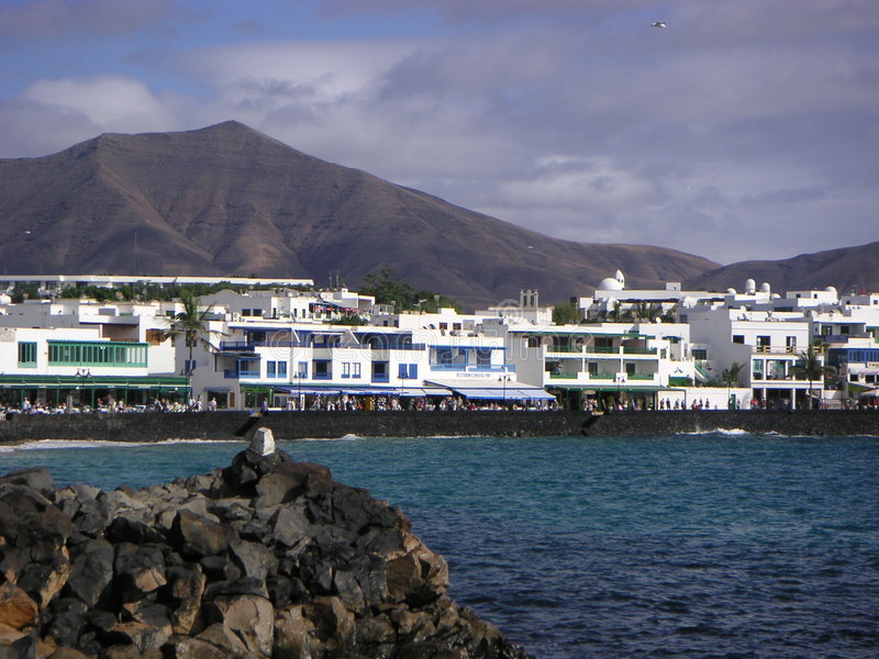 Playa Blanca, Lanzarote. Black lava stone, blue-green sea, white houses, black mountain, sky. This is Playa Blanca, Lanzarote stock images