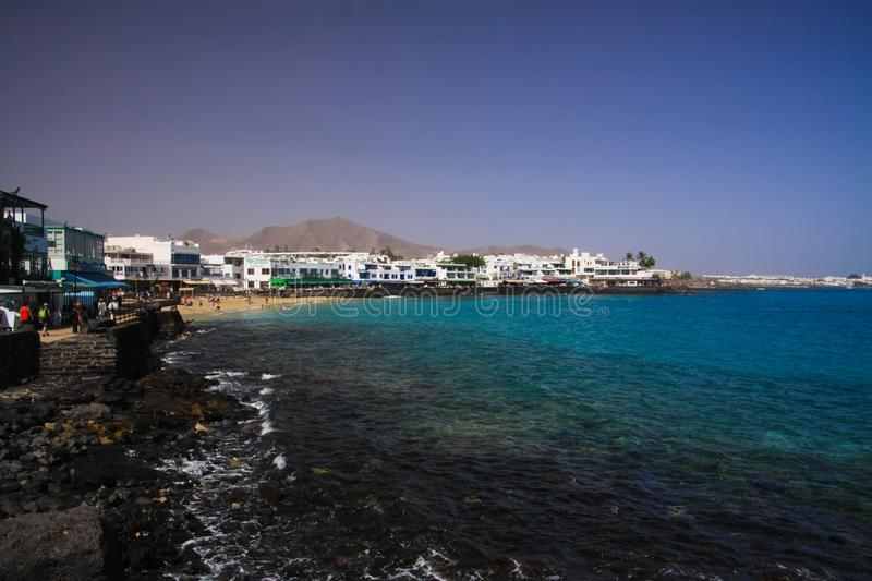 PLAYA BLANCA, LANZAROTE - JUIN 9. 2019: View on cityscape with promenade at ocean in lagoon with white houses. View on cityscape with promenade at ocean in royalty free stock images