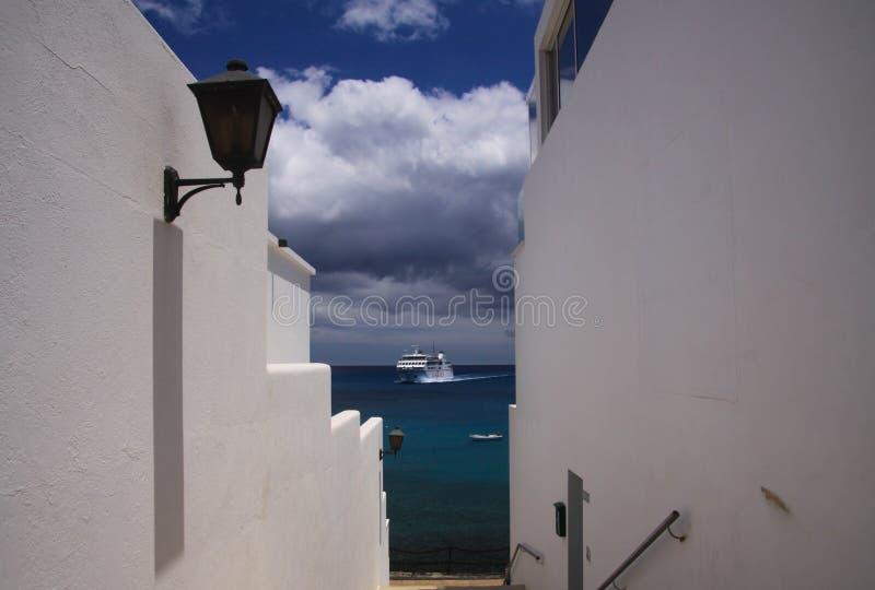 PLAYA-BLANCA, LANZAROTE - JUNI 14 2019: Sikt längs vita väggar av huset på färjan som ankommer från Fuerteventura arkivfoto