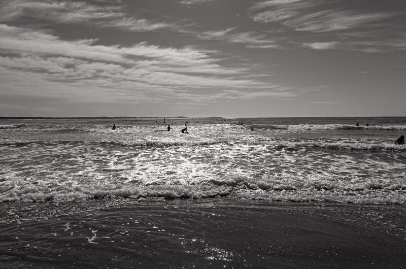 Playa blanco y negro con las siluetas de la gente imágenes de archivo libres de regalías