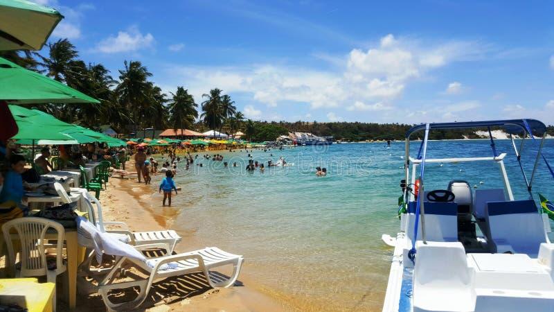Playa brasileña por completo de la gente, de paraguas y de barcos fotos de archivo