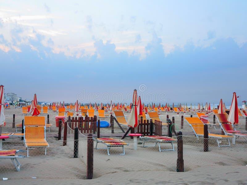 Playa cómoda con las camas del sol y los paraguas anaranjados fotos de archivo