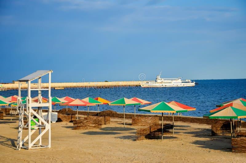 Playa cerca del mar - camas del caballete, paraguas del verano para la sombra, l imagen de archivo libre de regalías