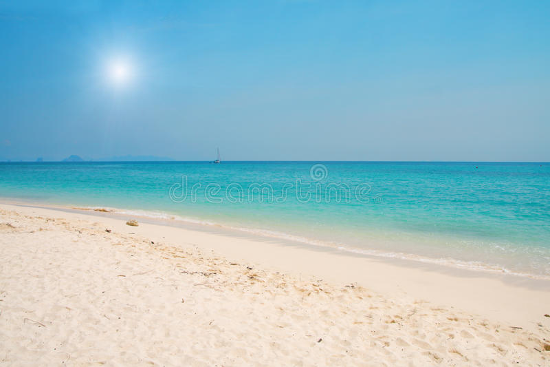 Playa con la arena blanca y el mar azul imagenes de archivo