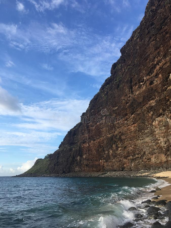 Playa con la arena, Lava Rocks, y los acantilados en la costa de NaPali en la isla de Kauai, Hawaii imagen de archivo