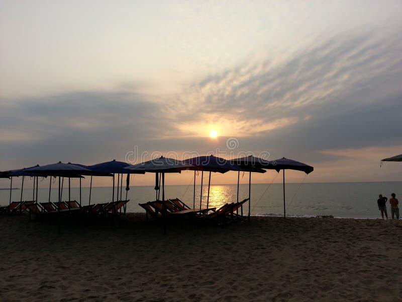 Playa con la gente, los paraguas y las sillas de la silueta imagenes de archivo