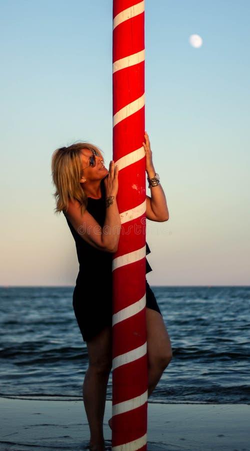 playa con la mujer rubia y un polo que amarra rojo Paisaje maravilloso imagen de archivo