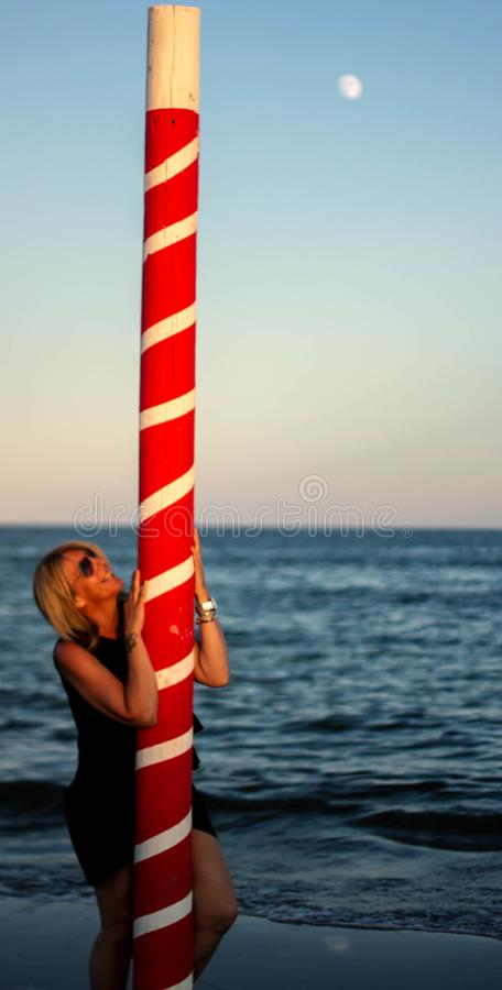 playa con la mujer rubia y un polo que amarra rojo Paisaje maravilloso fotografía de archivo libre de regalías