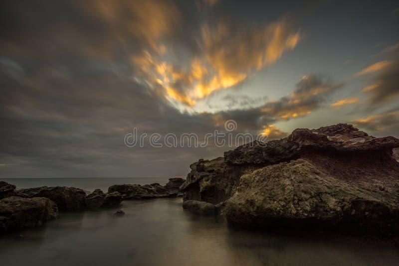 Playa con las piedras grandes de la lava en la puesta del sol fotografía de archivo