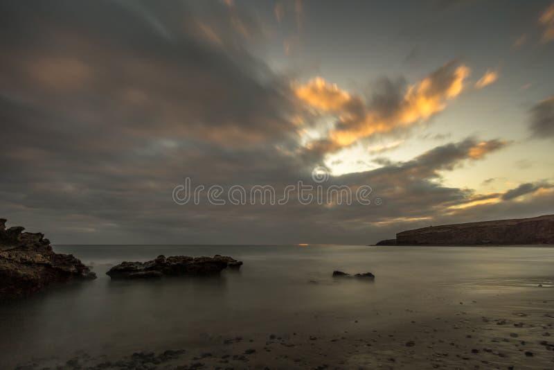 Playa con las piedras grandes de la lava en la puesta del sol imagen de archivo