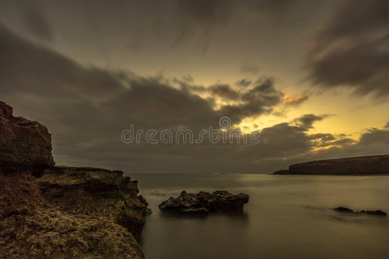 Playa con las piedras grandes de la lava en la puesta del sol fotos de archivo libres de regalías