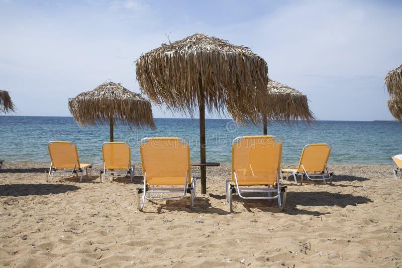 Playa con las sillas amarillas imagen de archivo