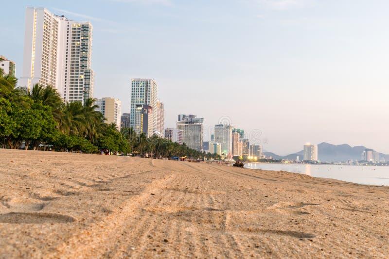 Playa con los ?rboles tropicales en orilla y el edificio alto en el amanecer foto de archivo libre de regalías