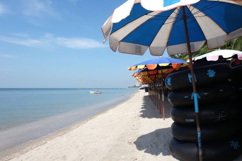 playa con los anillos de la nadada/los tubos de la nadada y el barco de plátano imagen de archivo