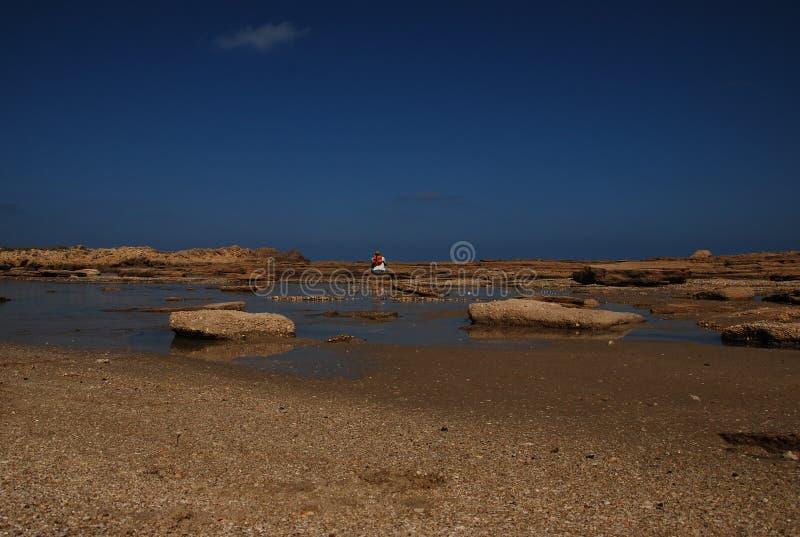 Playa con rocas y un hombre imagen de archivo