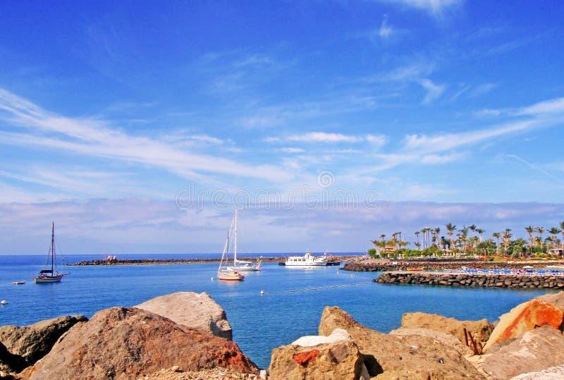 Playa de Arguineguin con los barcos y las palmeras foto de archivo