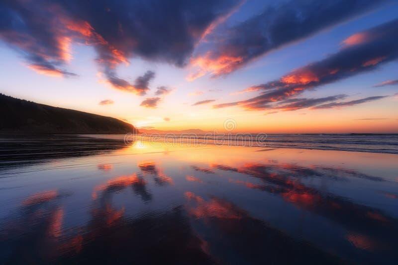 Playa de Barinatxe con reflexiones de la nube en la puesta del sol fotos de archivo libres de regalías