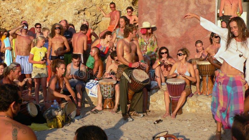 Playa de Benirras, Ibiza, España - 23 de julio de 2006: Porciones de gente que mira la puesta del sol mientras que toca los tambo imagenes de archivo