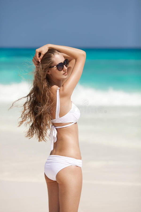 Playa de bronce de Tan Woman Sunbathing At Tropical fotos de archivo