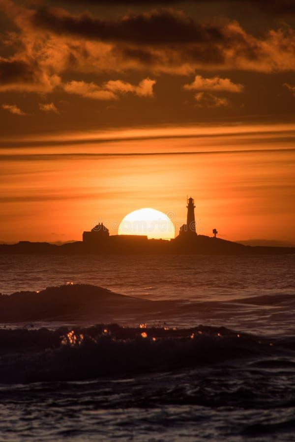 Playa de Hellstø de la puesta del sol con el rojo Noruega del amarillo del faro imagen de archivo