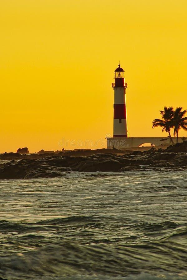 Playa de Itapua del faro con el cielo amarillo en la puesta del sol, Salvador, Bahía, el Brasil imagen de archivo libre de regalías