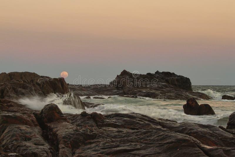 Playa de Itapua en la oscuridad con la luna entre las rocas, Salvador, Bahía, el Brasil fotos de archivo libres de regalías