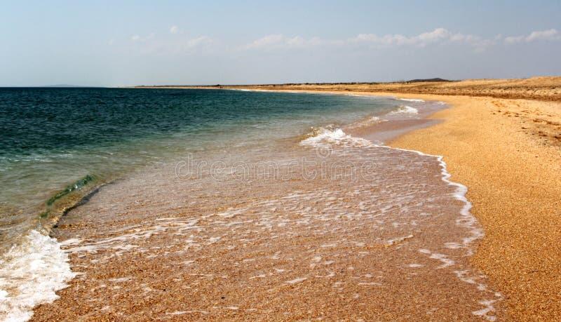Playa de la arena y fondo transparente del agua fotos de archivo