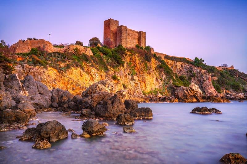 Playa de la roca de Talamone y fortaleza medieval en la puesta del sol Maremma Arg imagenes de archivo