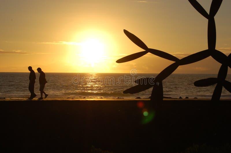 Playa De Las Americas. Two people on the boardwalk royalty free stock image