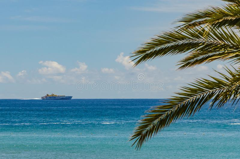 Playa de las Americas, Tenerife - April 13, 2016: Express ferry. From Tenerife to La Gomera on the blue Atlantic ocean with green palm branches in foreground stock photo
