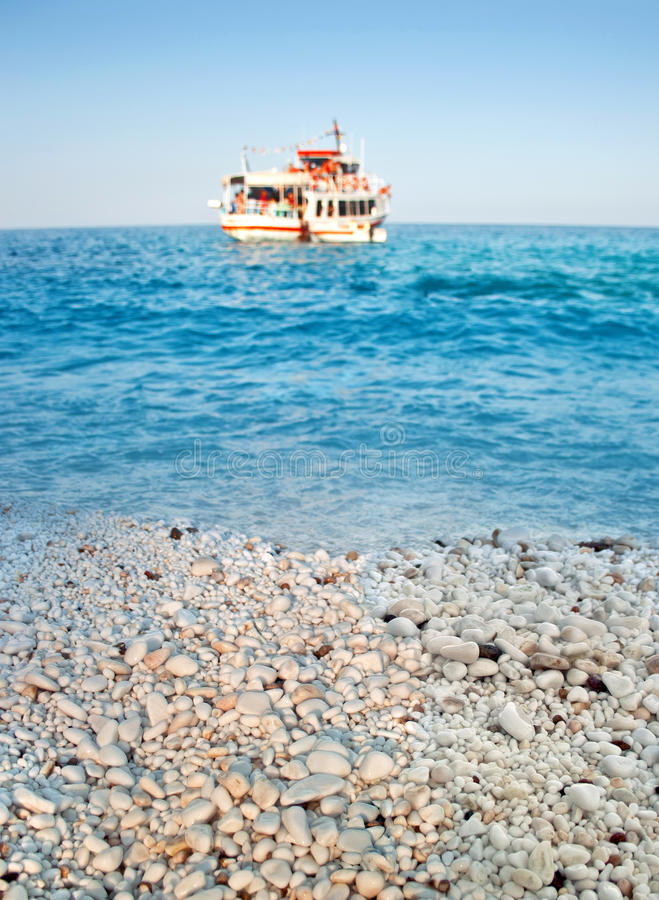 Playa de mármol griega, mar azul y barco de la travesía foto de archivo